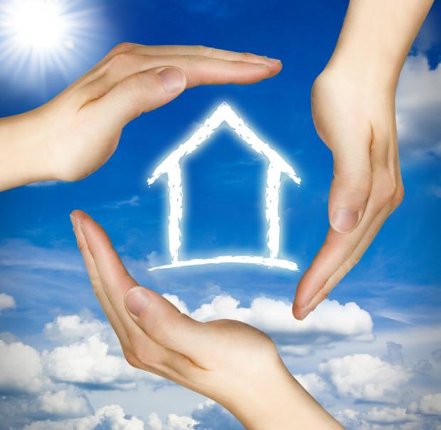 Schützende Hände um ein Haus